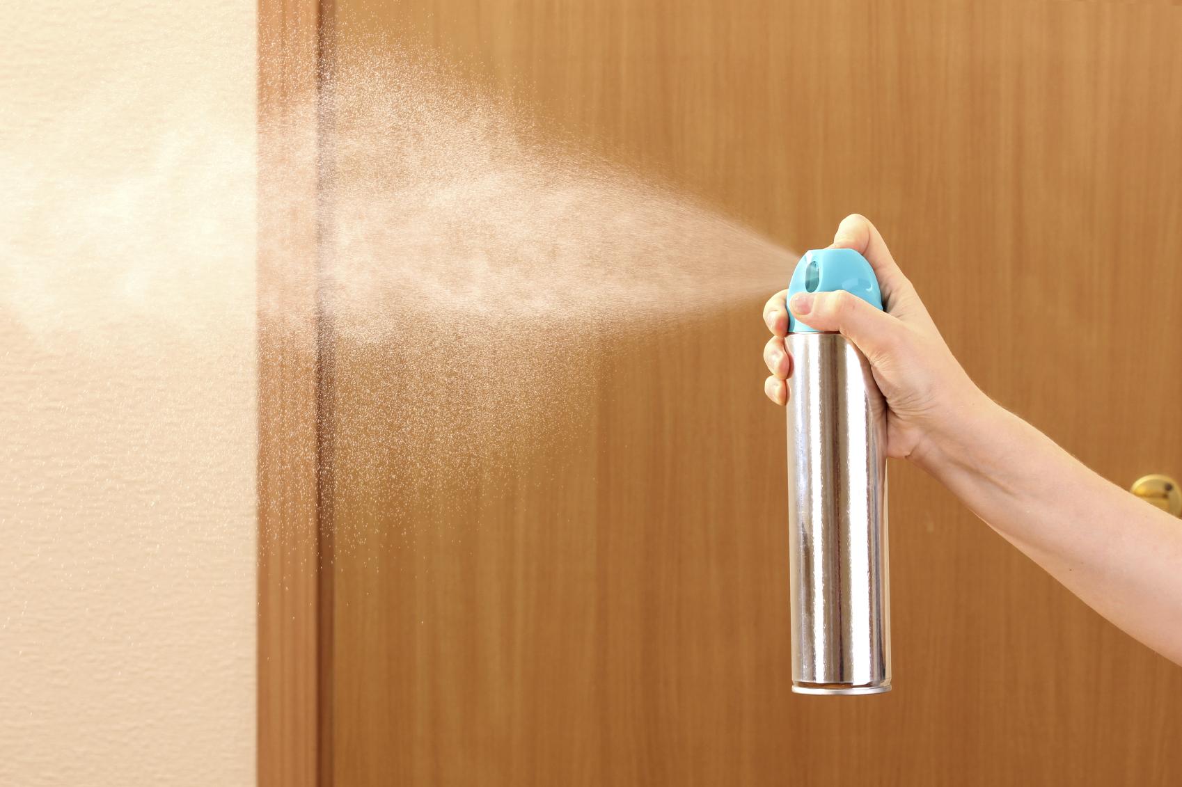 Sprayed air freshener in hand on room background