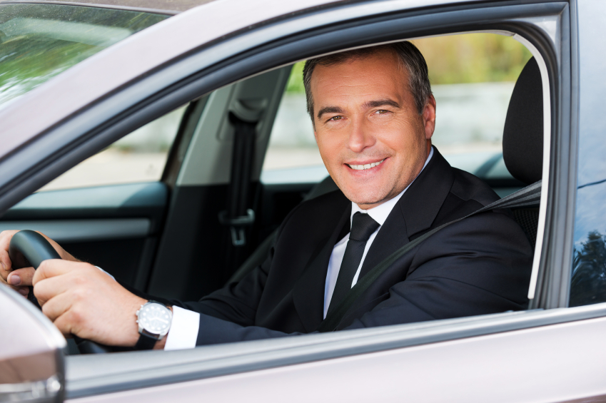 Feeling comfortable in his new car. Cheerful mature man in formalwear driving car and smiling
