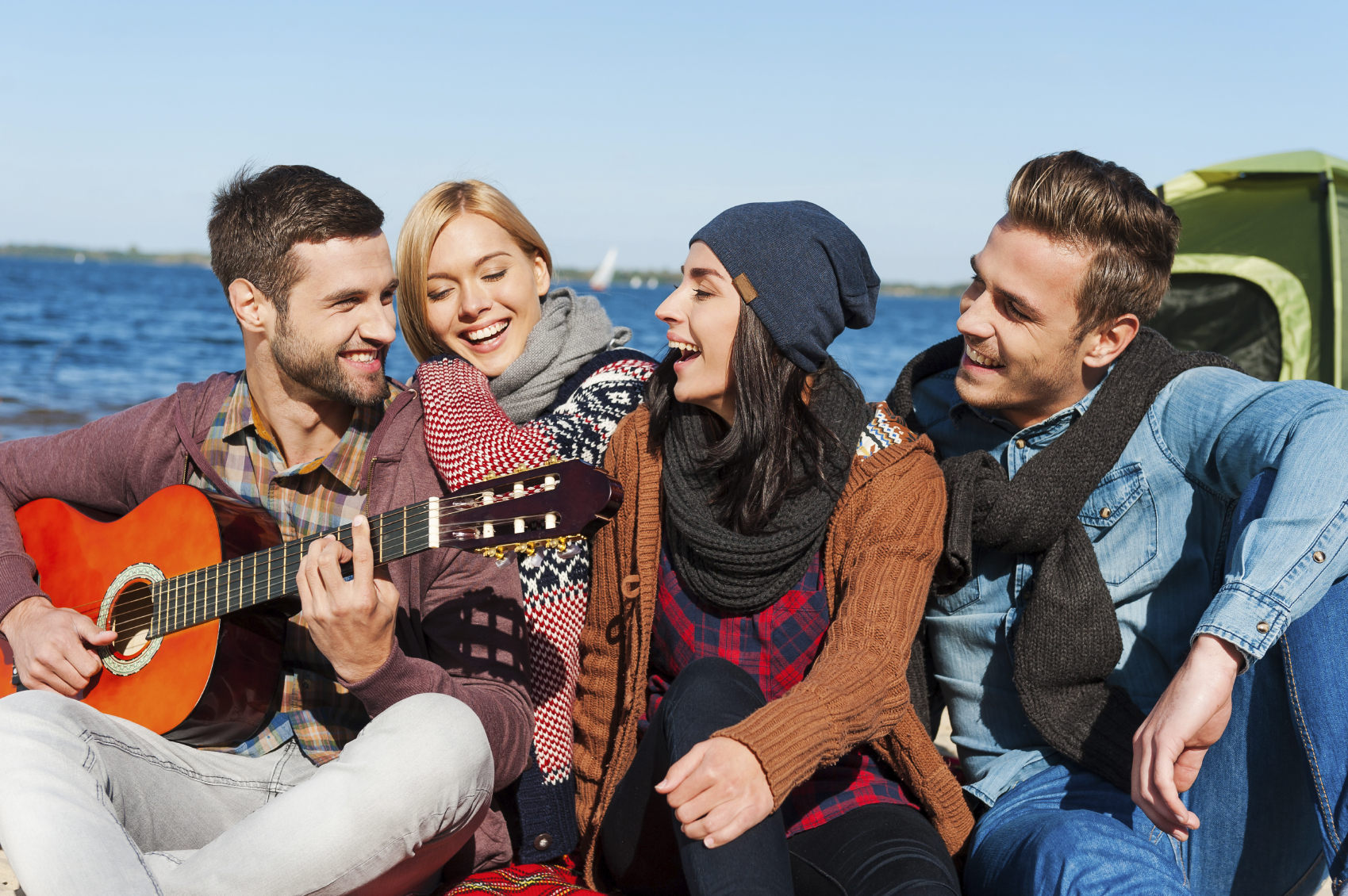 Just friends and guitar. Group of young cheerful people sitting at the riverbank together while young handsome man playing guitar and smiling